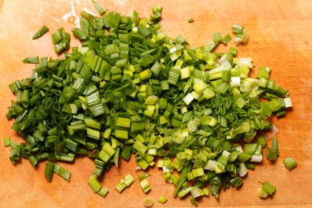 cutted: Fresh green onions on a cutting board. Cutted Green Onions On Wooden Cutting Board Stock Photo