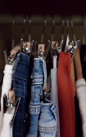ahorcada: Various clothes hanged in wardrobe. Clothes hang in the closet. Jeans and skirts on chrome plated clothespins. Tightly hanging clothes in the wardrobe.