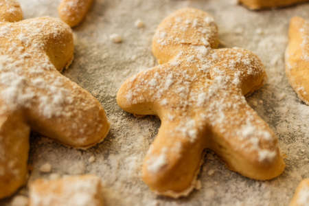 gingerbread man: Cookies in the form of men, animals and snowflakes on a baking sheet. Cookies sprinkled with powdered sugar. Traditional Christmas cookies with spices and powdered sugar in the form of holiday symbol spruce, stars, men, canes on a baking sheet