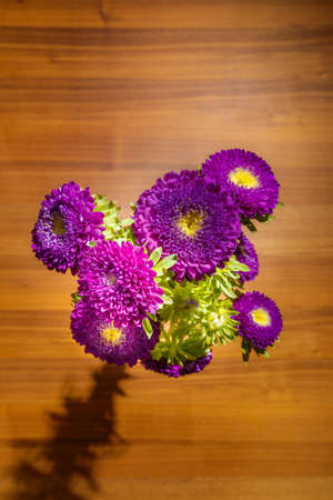 Purple aster on a wooden background. Flowers view from above on an oak table. Fresh young asters flowers in a glass vase on a wooden background. Purple small asters. Asters view from above