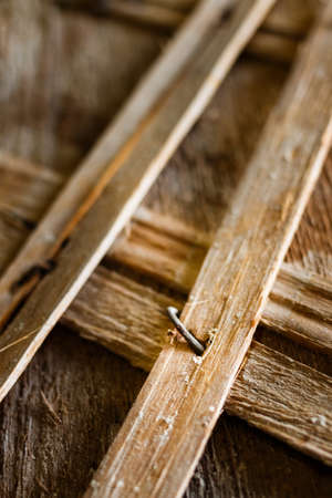 rusty nail: Wooden shingles. Old Wooden slats. Old wooden structures with rusty nails. Wooden vintage designs. Beams with a crate of thin strips.