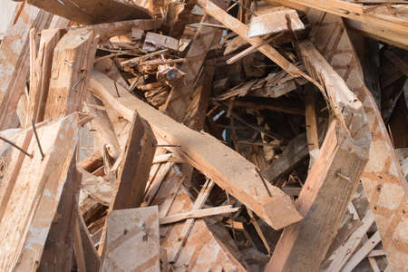 Pile of planks after renovation of building. Heap of broken boards with nails. Old boards. Repair of the building. Construction garbage