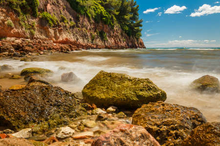 Rocky seashore. Summer Day on Sea Travel Time Vocation. View to mountain rocky seashore from water sea. Beautiful water landscape Summer Day. Beautiful wild coastline of Spain.