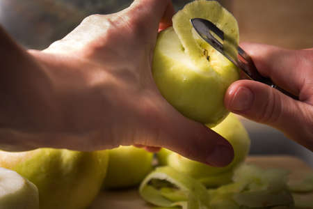 Female hands peeling skin off of green apple using a paring knife. Peel the Skin Off Apples. Woman cuts off the peel of an apple. Garden apples. Golden apples. Farm products. Juicy fruit.