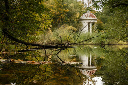 background texture: Classical white rotunda on the shore of a pond. Autumn Park. An ancient graceful rotunda with columns. Autumn landscape with forest, pond and architecture. Stock Photo