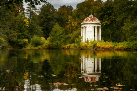 rotunda: Classical white rotunda on the shore of a pond. Autumn Park. An ancient graceful rotunda with columns. Autumn landscape with forest, pond and architecture. Stock Photo