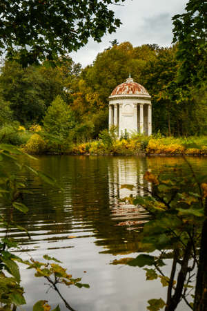 the collapsing: Classical white rotunda on the shore of a pond. Autumn Park. An ancient graceful rotunda with columns. Autumn landscape with forest, lake and architecture. Stock Photo