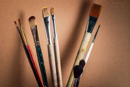 Artistic brushes on the background of corrugated cardboard. The artists tools. Stock Photo