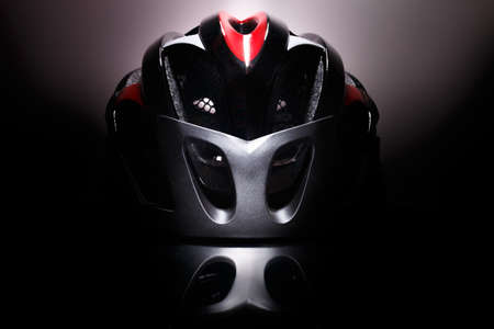 Future technologies. Aerodynamic aggressive forms on a black background. Bicycle mountain bike safety helmet. Stock Photo