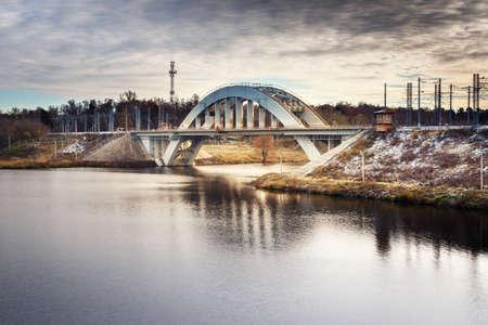 Railway bridge across the river in autumn. Arch of the railway bridge. First snow. Russia. Moscow. Banco de Imagens