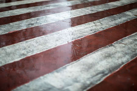 Red and white diagonal road markings for fire trucks. Rainy weather on a city street Banque d'images
