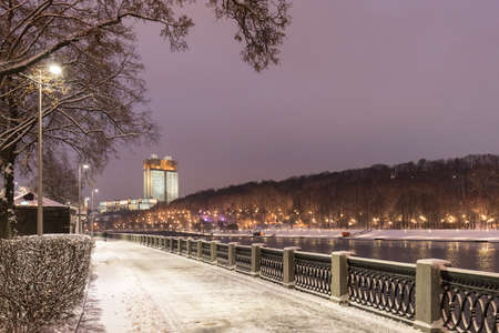 Moscow. Russia. Winter snow-covered city landscape. View from the Luzhnetskaya embankment to the Muskva River, Vorobyovy Gory and the Russian Academy of Sciences building with an evening illumination. Zdjęcie Seryjne