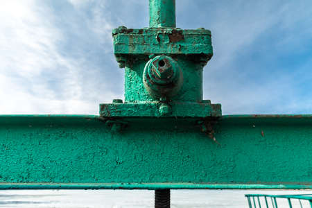 Old green metal structure with peeling paint on the background of sky. Detail of industrial design.