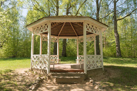 Wooden summerhouse in the park in the summer.. Outdoor wooden gazebo over summer landscape background