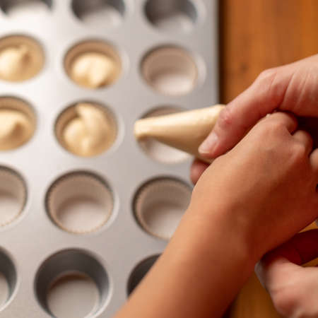 Mom and daughter cook cupcakes. Women's and children's hands squeeze the cream in the form for cupcakes. Concept happy family