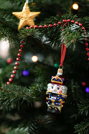 The nutcracker on a fir-tree. Christmas decoration of a fir-tree. New Year's background. Christmas decorations and toys. Christmas tree with toys. Stock Photo