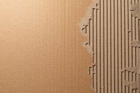Texture de carton ondulé avec bords déchirés. Emballage en carton texturé. Texture carton. Fond de maille en carton