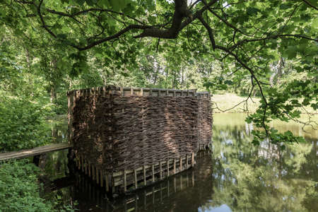 Wooden building on the shore of the pond. Wicker building in the forest. Bathing building.