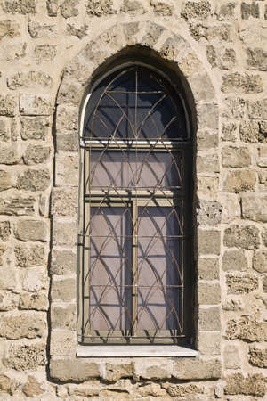 Antique arched window in a stone wall photo