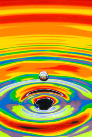 black hole produced by a falling droplet on a multicolored water surface photo