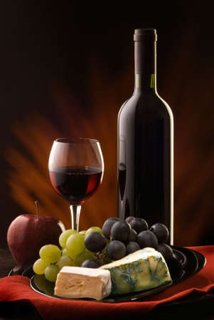 composition with glass and bottle of red wine with various types of cheese and grapes photo