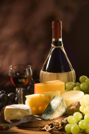 Glass and bottle of red italian wine with various types of cheese and garnishes photo