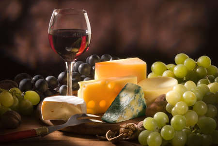 Glass of red wine with various types of cheese and garnishes photo