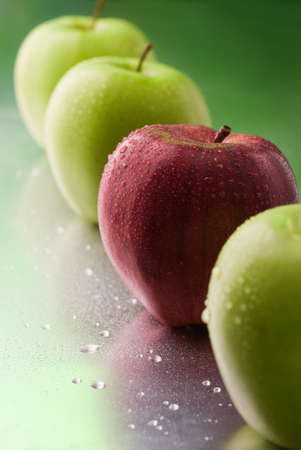 distinguish: single red apple in a row on a green background