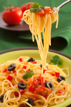 tészta: swirl of spaghetti on a fork garnished with sauce and leaf Stock fotó