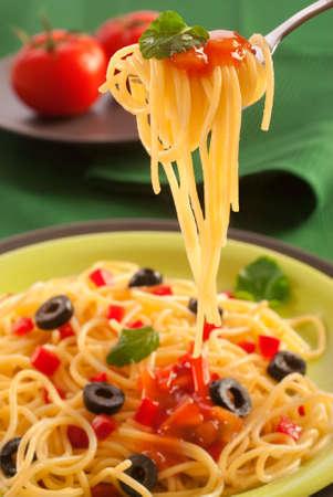 spaghetti: wervel van spaghetti op een gegarneerd met saus en leaf fork