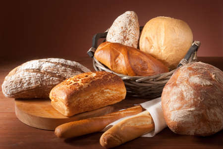 sustenance: still-life assortment of baked bread over brown background Stock Photo