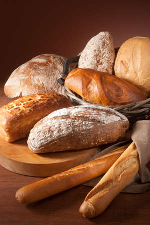 still-life assortment of baked bread over brown background photo