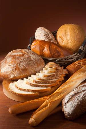 canasta de panes: bodeg�n surtido de pan horneado sobre fondo marr�n