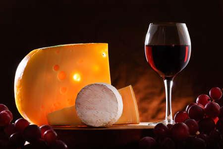 vinos y quesos: composici�n con las uvas, copa de vino tinto y varios tipos de queso Foto de archivo