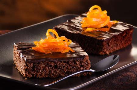 trozo de pastel: Brownie de chocolate hecho en casa en una placa oscura contra un fondo oscuro