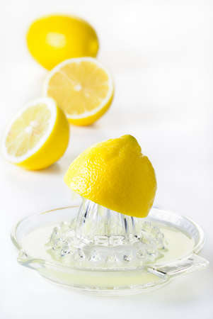 squeeze: Glass citrus squeezer with lemons and juice on a white table