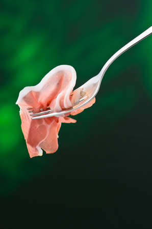 mouthful: Slice of raw ham on a fork Stock Photo