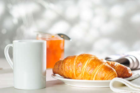 apricot jam: breakfast croissant, apricot jam and cup of hot drink
