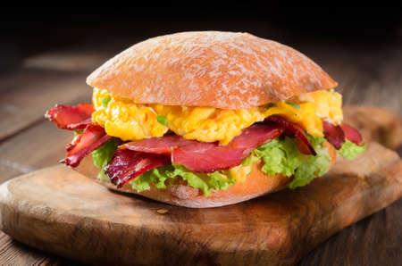 ciabatta sandwich with scrambled eggs, crispy bacon and lettuce leaves Foto de archivo