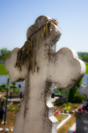 life after death: Dry wreath on a white stone cross in a cemetery Stock Photo
