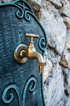 source of iron: Decorative iron tap on a stone wall Stock Photo