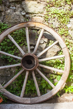 old wood farm wagon: Old wooden wheel leaning up against stone wall