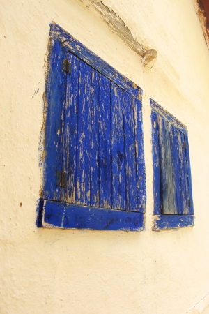 Two blue wooden windows on a white wall  Blue Roller blind  Blue Window - shade photo