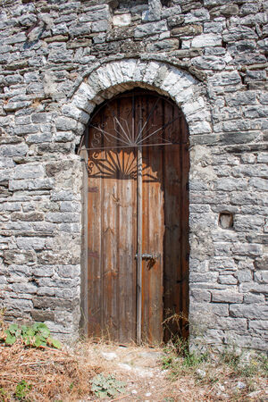 Ancient bown wood door in Gjirokaster photo