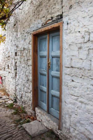 Ancient blue wood door on a tight alley of Berat photo