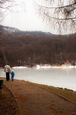 Winter scenery with a father and daughter walking on their way near a frozen lake surrounded by mountains and forests  photo