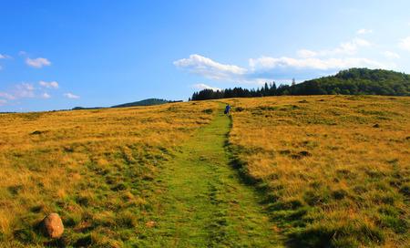 Freedom life path metaphor. Woman walking alone on a beautiful mountain path photo