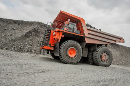 Orange mining vehicle driving in the pit photo