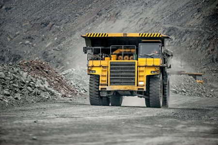 Yellow mining vehicle driving in the pit photo