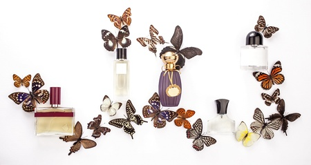 A composition of perfume bottles with butterflies on white background Stock Photo